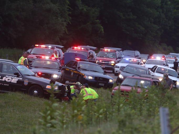 EMS personnel tend to one of the injured at the end of a police chase that ended with several police vehicles stopping a red Ford SUV southbound on Interstate 684 at the Westchester-Putnam boarder in the town of Southeast July 13, 2014.