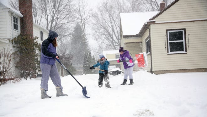 Students from the West Irondequoit Central School District use their snow day to shovel driveways in their neighborhood.