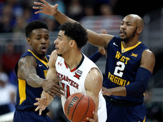 West Virginia's Daxter Miles Jr., left, and Jevon Carter (2) pressure Texas Tech's Zach Smith during the first half of an NCAA college basketball game in the Big 12 men's tournament Friday, March 9, 2018, in Kansas City, Mo. (AP Photo/Charlie Riedel)