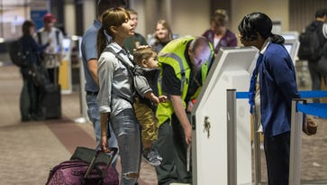 Anali Hernandez, 17, carries her son, Eli Borboa, 1, while talking with American Airlines agent Kawana Davis at Phoenix Sky Harbor International Airport on Tuesday, Nov. 24, 2015. She had not encountered extra security.