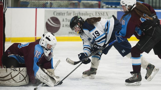 North Country goalie Mikaella Doran (30) makes a save as Mount Mansfield's Anna Burke (19) tries to score during Wednesday night's game at the Essex Skating Facility.