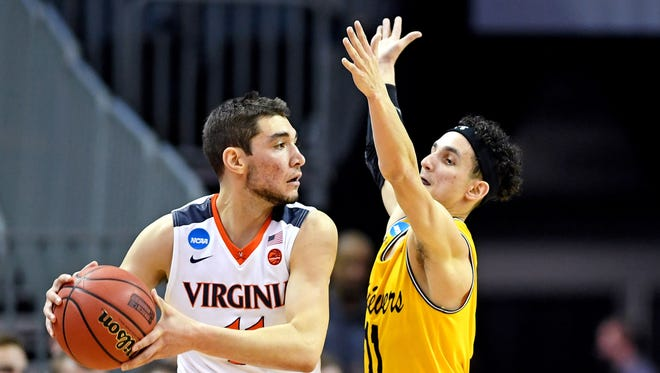 Mar 16, 2018; Charlotte, NC, USA; Virginia Cavaliers guard Ty Jerome (11) handles the ball against UMBC Retrievers guard K.J. Maura (11) during the first half in the first round of the 2018 NCAA Tournament at Spectrum Center.