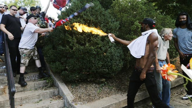 """FILE - In this Aug. 12, 2017, file photo, a counter demonstrator uses a lighted spray can against a white nationalist demonstrator at the entrance to Lee Park in Charlottesville, Va. There has been no reset, no moment of national healing. One year after blaming """"both sides"""" for violent clashes between white supremacists and counterprotesters, President Donald Trump stills flirts with racially tinged rhetoric _ and feels little blowback from Republican leaders or GOP voters when he does. Black leaders and Democrats argue Trump's tone and actions on race have gotten even worse in the months since the clashes in Charlottesville, Virginia. (AP Photo/Steve Helber, File)"""