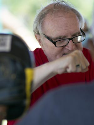 Galesburg's Dave Beversdorf throws a punch at director Carlos Duncan during Rock Steady boxing on Friday, July 17, at Rotary Park.