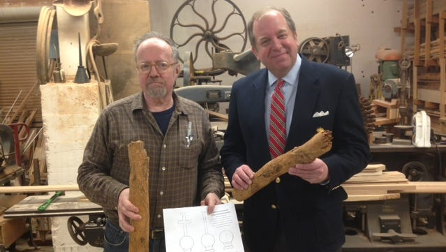 Baltimore woodwright Thomas Brown, left, and Scott Watkins, officer with the Society of Colonial Wars in the State of Maryland, hold roots from the last standing Liberty Tree that Brown would whittle into crosses to be placed in the chapel in St. Mary's City representing Maryland's history.