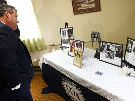 Gov. Chris Christie looks at photos of City of Angels recovered addicts after a stop at the Manasquan Recreation Annex Thursday, September 21, 2017.  He was there for a roundtable discussion with parents of recovering addicts.