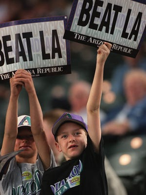"Trevor Stone, 7, and Drew Stone, 8 of Phoenix wave their ""BEAT LA"" signs before the Diamondbacks vs LA Dodgers game at Bank One Ballpark."