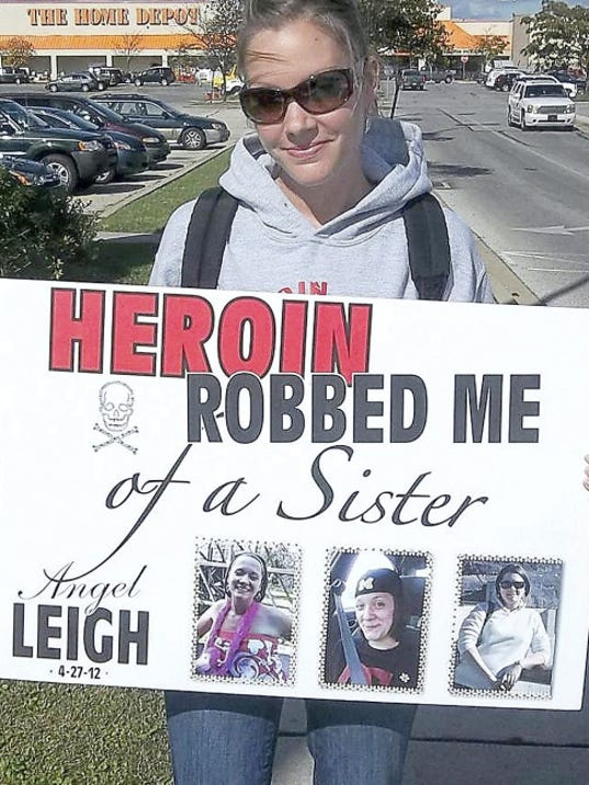 Angela Lyle of Wrightsville, right, poses with a sign memorializing her sister, Leigh Baxter, who died in 2012. Lyle, like other family members who have lost loved ones to heroin, is now active in groups that fight against heroin addiction.