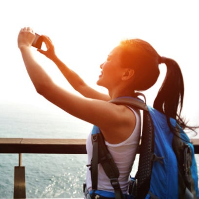 woman hiker takes a photo by the seaside