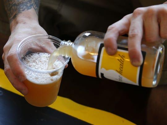 Ryan Kelly pours fermented tea made at Fine Health Kombucha.