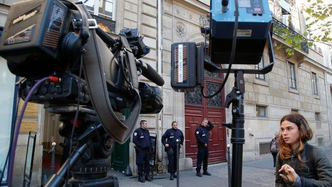 In this Oct.3, 2016 file photo, French police officers and a TV crew stand outside the residence of Kim Kardashian West in Paris. Police in Paris say Monday Jan.9, 2017 that 16 people have been arrested in connection with the October theft of more than $10 million worth of jewelry from Kim Kardashian West.