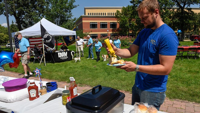 Shawn Kamphuis has lunch at the St. Cloud State University Students Veterans Association fundraiser Saturday, Aug. 19, in Barden Park. Money raised goes to an emergency relief fund for student veterans and military families.