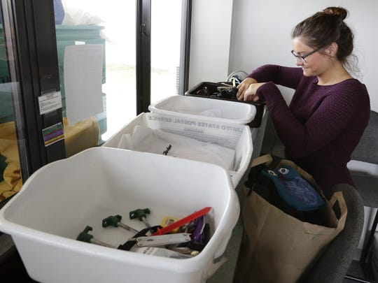 Sarah Yeoman of the Experimental Aircraft Association looks items that visitors lost or left behind during AirVenture 2015. Everything from cameras, credit cards, money, keys, jackets, motorcycle helmet, knives, reading classes, camp chairs, umbrellas and more are in the lost and found.