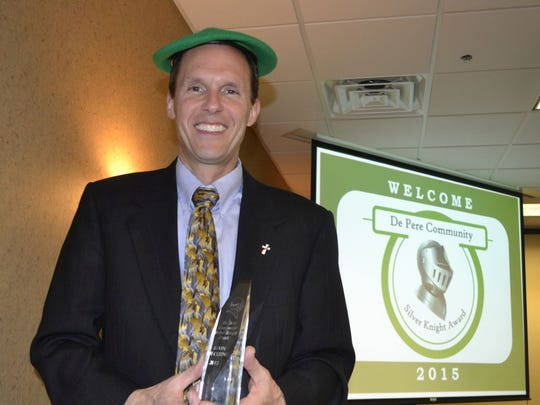 Kevin DeCleene wears the traditional green beret and holds a crystal trophy that go to the winner of the De Pere Community Silver Knight Award after Monday night's award ceremony at Swan Club in De Pere.