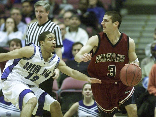 Penn's David Klatsky, a Holmdel native, looks to  pass while being guarded by Seton Hall's Andre Barrett in 2000.