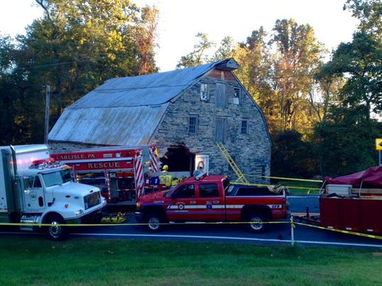 Police and fire officials respond to the scene of a car that crashed into a barn at the intersection of Mountain and Mill Roads in York Springs on Sunday, October 11, 2015.