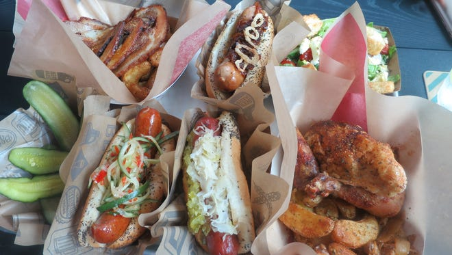A typical Beerhaus spread features a house pickle side, Hot Link, City Dog, rotisserie half chicken, side salad, bratwurst and porchetta (counterclockwise from front left).