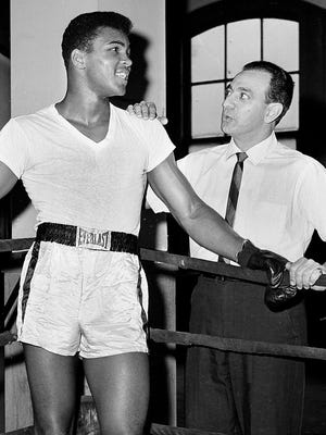 FILE - In this Feb. 8, 1962, file photo, young heavyweight fighter Cassius Clay, who later changed his name to Muhammad Ali, is seen with his trainer Angelo Dundee at City Parks Gym in New York.