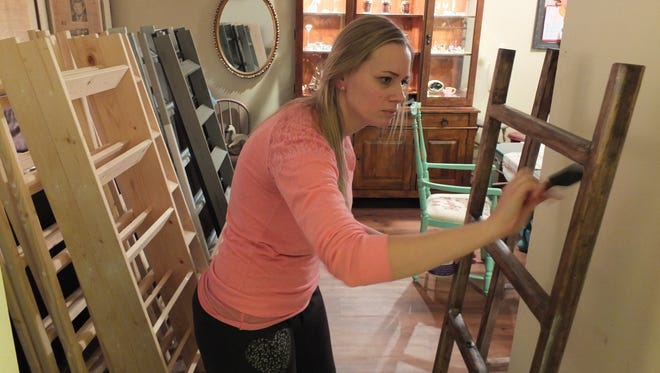 Melissa Geib works on a project in her apartment while surrounded by others in various stages of completion.