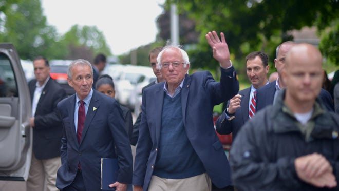 Sen. Bernie Sanders waves to supporters as he heads back toward his home after addressing the news media about a meeting on Sunday at his Burlington home with supporters and advisers on the future of his bid for the Democratic presidential nomination.