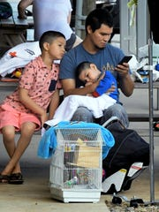 Gabriel Ruelas makes a call while sitting with his sons Dillon, 2, and Christopher, 8, and daughter Quetzalli,1, in car seat, and the family's pet birds after a two-alarm fire at their row house in the 300 block of Pattison Street Thursday, June 28, 2018. The fire was reported around 4:15 a.m. and took about 30 minutes to control, according to York City Fire Chief Dave Michaels. He said 4 adults and 6 children were displaced after the fire and the Red Cross is assisting them. Michaels said one occupant, a 12-year-old girl, was transported to the hospital for smoke inhalation and one firefighter was treated for a minor burn at the scene. Bill Kalina photo