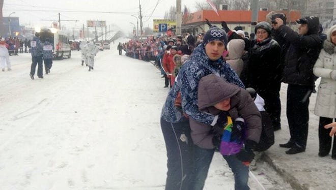 In this photo provided by Pavel Lebedev, security personnel detain Lebedev, a gay protester, during the Olympic torch relay in the city of Voronezh.