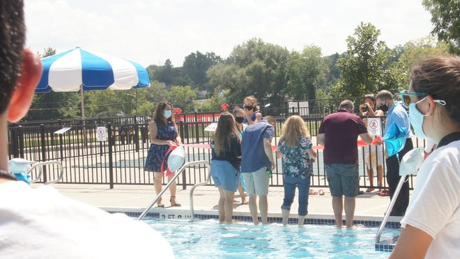 "With two lifeguards watching, members of the Newton Town Council, (feet in the water), prepare for one of several ""ribbon-cuttings"" around the renovated pool on Tuesday afternoon."