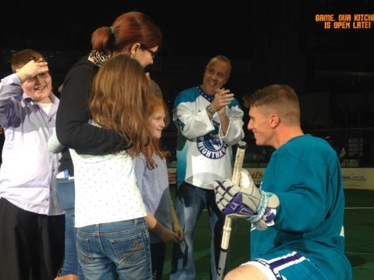 Sgt. Jesse Fuller, right, surprises his family at a Knighthawks game on Dec. 12, 2015.