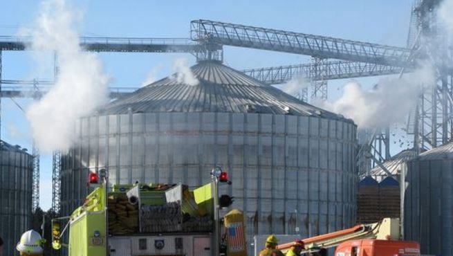 Smoke pours from holes in a grain bin in Brokaw after an explosion in January 2011.