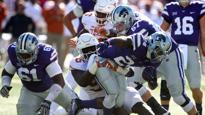 Kansas State running back Charles Jones (24) is tackled by Texas Longhorns defensive tackle Poona Ford (95) during during Saturday's game in Manhattan, Kan.