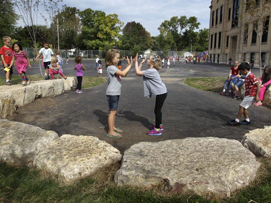 Tatum Seefeldt (left) and Katie Wagner play on the newly landscaped playground last week at Columbus Elementary/Appleton Bilingual School.