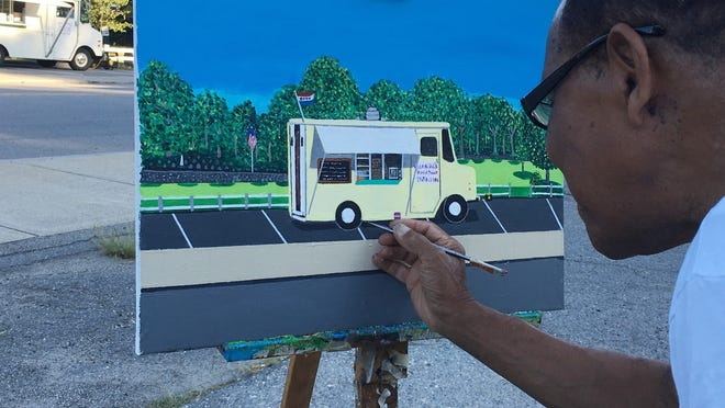 Lionel Reinford puts the finishing touches on a painting of a food truck across from Carter Park in Leominster in 2016.