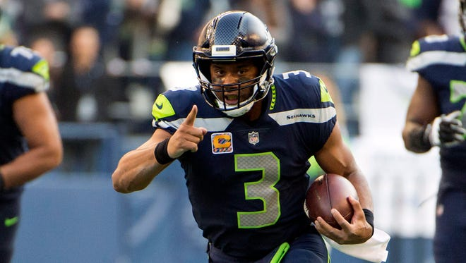 Seattle Seahawks quarterback Russell Wilson (3) picks up a first down during the second half against the Houston Texans at CenturyLink Field.