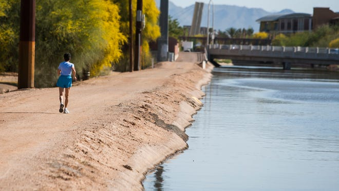 A runner uses the path along the canal near Fifth Avenue and Goldwater in Scottsdale. The canals once were used by kids water skiing on them.