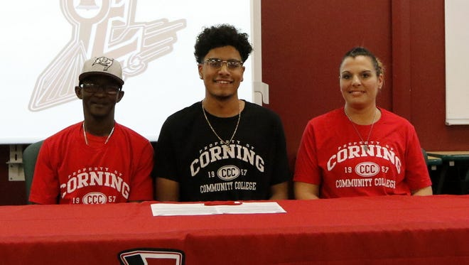 Jerick Guinta, center, signs to attend Corning Community College alongside his parents, Wayne and Jamie Driscoll, during a ceremony Thursday at Elmira High School.