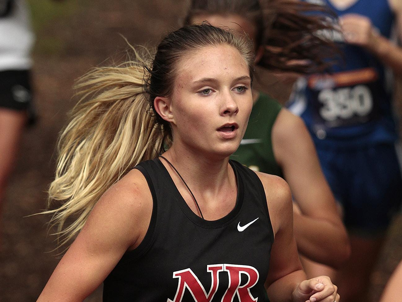 Melissa Lefler of New Richmond runs with the pack in the woods at Corwin Nixon Park Sept. 12.
