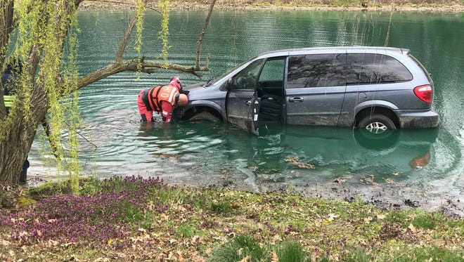 HPD Officer Bill Russell attaches a cable to a vehicle that had driven into the water near William and Mary Court