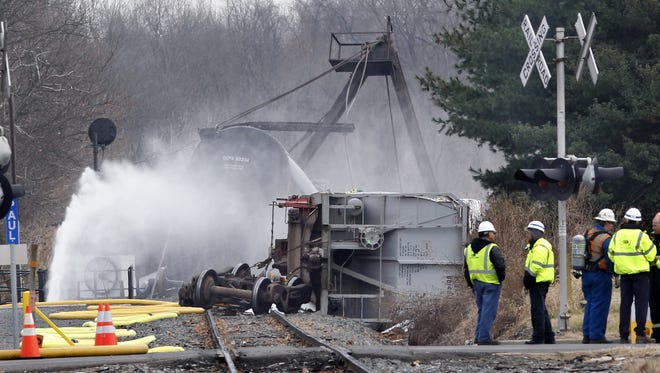 Water is sprayed on tanker cars from a freight train that derailed over Mantua Creek in  2012.