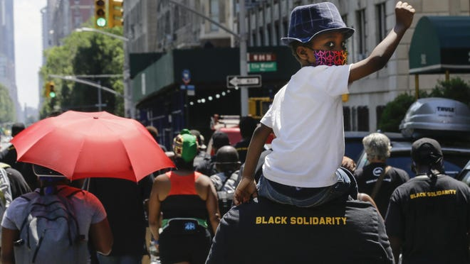 A man carries a child as they march near Central Park, during a Juneteenth celebration Friday, June 19, 2020, in New York. Juneteenth, the holiday celebrating the day in 1865 that enslaved black people in Galveston, Texas, learned they had been freed from bondage, more than two years after the Emancipation Proclamation.