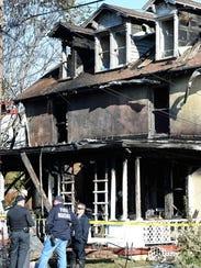 Fire investigators talk outside the scene of a fatal