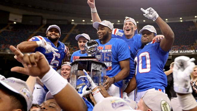 Louisiana Tech Bulldogs running back Kenneth Dixon (behind trophy) celebrates with teammates at the end of the 2015 New Orleans Bowl at the Mercedes-Benz Superdome. Louisiana Tech beat the Arkansas State Red Wolves, 47-28. Mandatory Credit: Chuck Cook-USA TODAY Sports