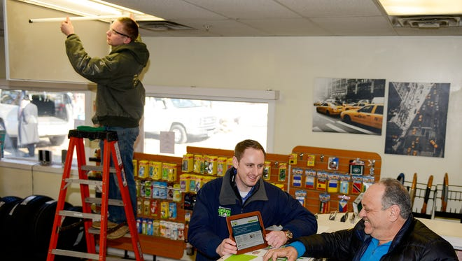 Adam Smith, Orange and Rockland employee, speaks with Sam Naemit, owner of Sam's Towing and Automotive in Spring Valley.