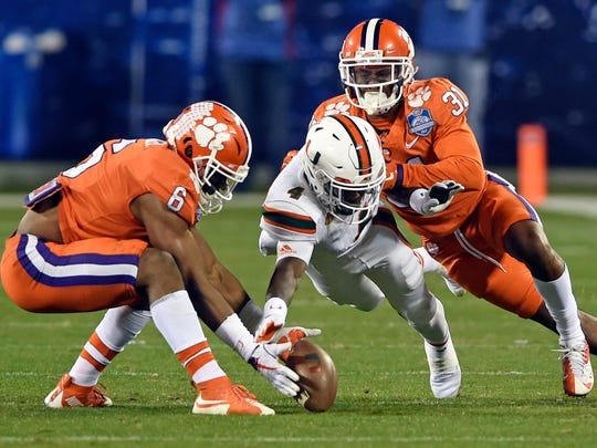 Clemson's Dorian O'Daniel (6) recovers a fumble by Miami's Jeff Thomas (4) as Clemson's Ryan Carter (31) closes in during the second half of the Atlantic Coast Conference championship NCAA college football game in Charlotte, N.C., Saturday, Dec. 2, 2017. (AP Photo/Mike McCarn)
