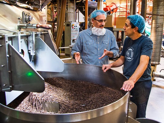 Hans Schatz, left, president and CEO of Cult Coffee Roasters, and Chris Marsitto, craft roast master, talk about a recent batch as coffee beans spill from a roaster at the plant in north Phoenix, Tuesday, October 11, 2016.