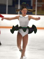 """Jackie Lewis, a member of the Lakeland Figure Skating Club, rehearses a scene from """"Grinchie on Ice."""" ."""