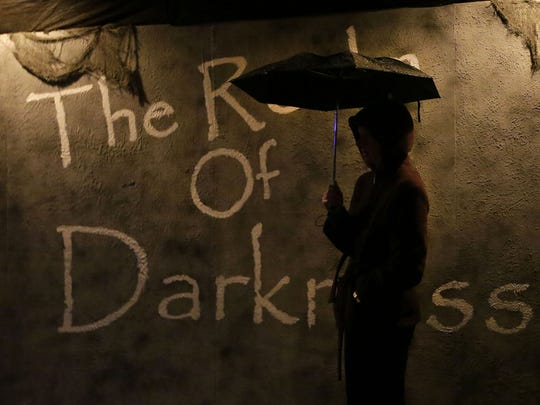 Kim Sullivan waits in the rain as she helps at The Realm of Darkness haunted house in Kaukauna. Her nephew, Ben Hurst, along with Dalton Polomis, are the creators of the scares that continue through the first weekend of November.
