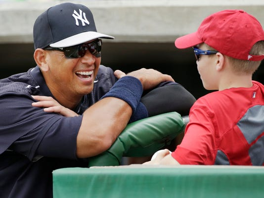 New York Yankees designated hitter Alex Rodriguez laughs as he talks with Spencer Woodall, 12, of Union, S.C., before the start of a spring training baseball game in Clearwater, Fla., Friday, March 27, 2015. (AP Photo/Kathy Willens)