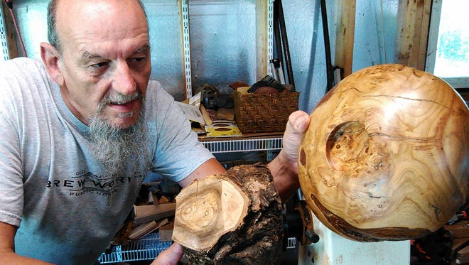 Roger Kiefer attaches a rough chunk of weeping cherry wood to his lathe, comparing it to a finished bowl fashioned from the same tree. He likes the character rough edges, knots and burled wood give his hand-crafted bowls.