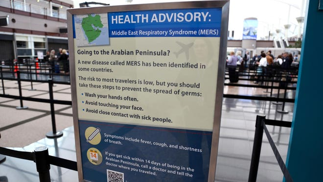 Sign at Denver International Airport shows signs posted on May 14 warning travelers about the danger of the MERS virus.