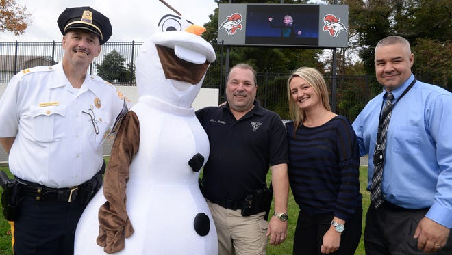 "A Disney princess is seen on the new screen at Gittone Stadium as Disney's ""Frozen"" plays behind Vineland police captain Tom Ulrich, costume character Olaf from the film, Vineland community police officer Joe Pagano, Vineland School's technology supervisor Katherine Rivera, and assistant superintendent Nathan Frey (from left) as they pose for a photo, Tuesday, Oct. 13.  The stadium's new screen will be used to show the film during an upcoming free family fun night hosted by Vineland Police."